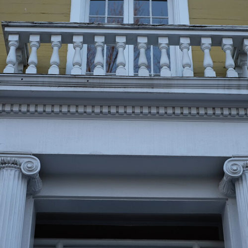 white railing owner top of two white columns