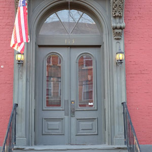 Double wooden door with glass top above it on red brick building