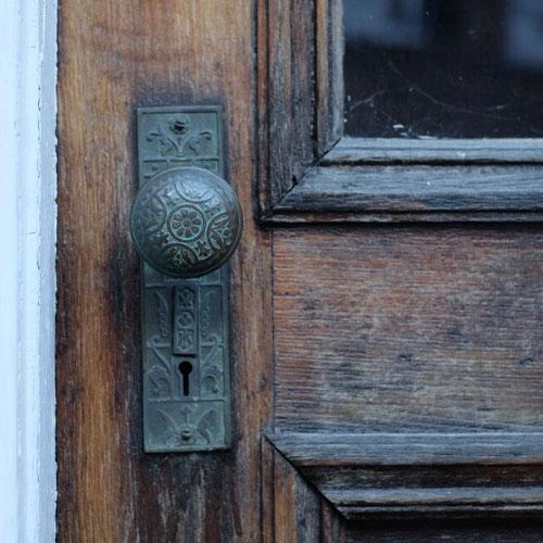 Ornate door handle on old wooden door