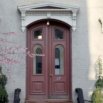 brick house wooden door plants