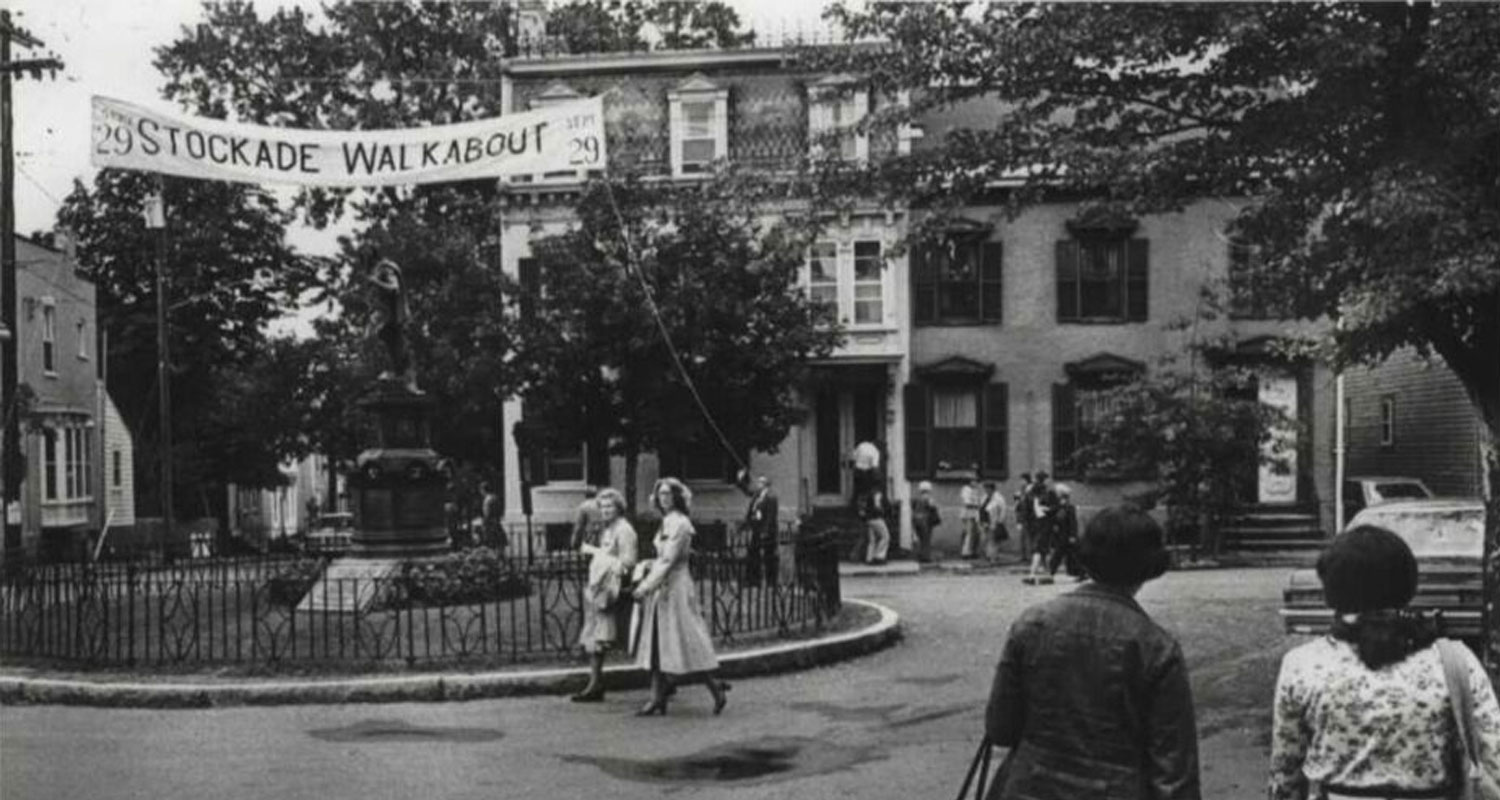 old photo of stockade walkabout with people around lawrence statue and road in black and white